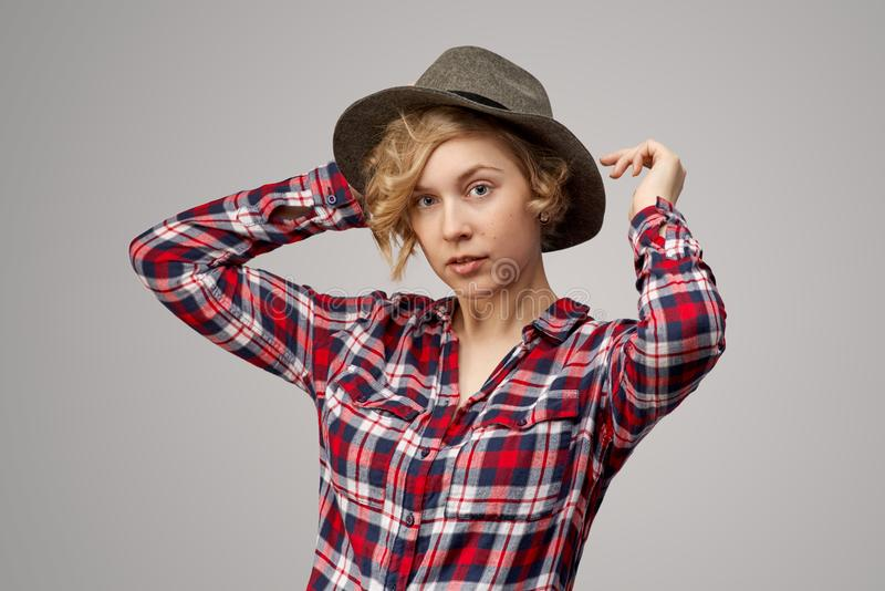 Attractive curly blonde in a plaid shirt and cowboy hat looks closely at the camera with a calm neutral expression. stock photo