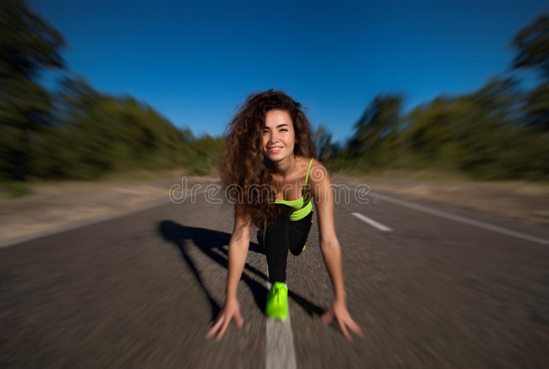 Attractive curly girl athlete doing morning exercises outside. royalty free stock image