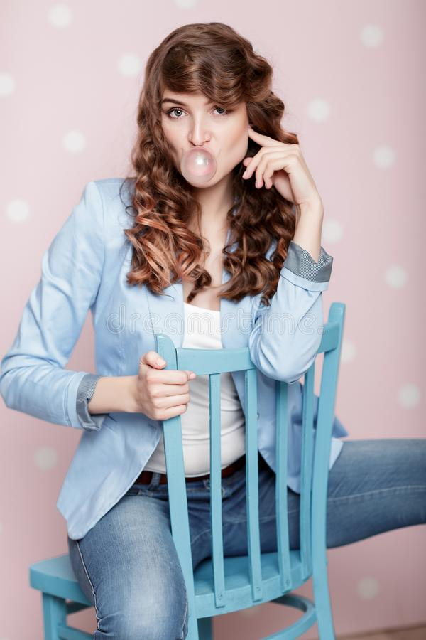 Woman doing bubble with chewing gum. Attractive curly woman doing bubble with chewing gum stock photo