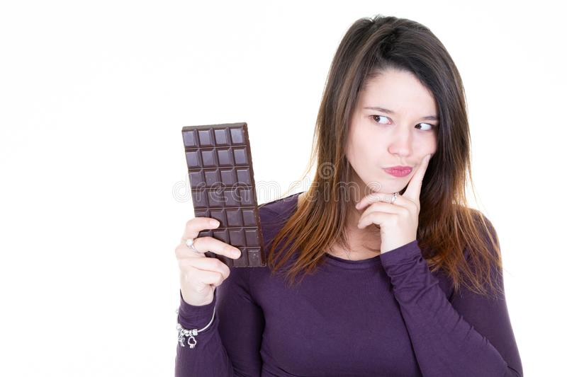 Attractive cute young woman with bar chocolate looking with temptation. An Attractive cute young woman with bar chocolate looking with temptation stock photography