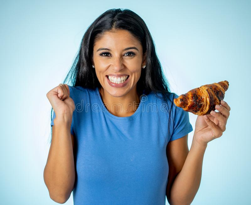 Attractive cute young woman with a chocolate croissant looking at it happy with temptation. Beautiful young cute and happy latin woman in casual clothes holding stock photography