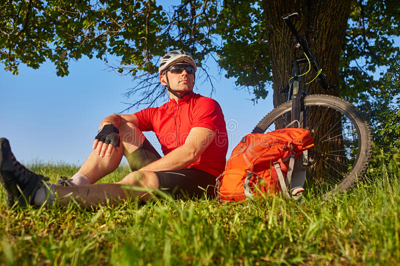 Attractive cyclist in the helmet sitting on the green meadow near the cycle in the countryside. royalty free stock photography