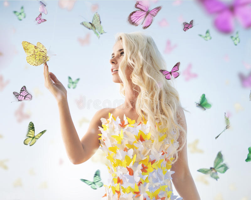 Attractive delicate blonde playing with butterflies stock image