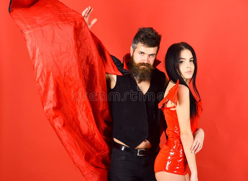 Attractive demon concept. Couple on strict face play role game. Vampire in cloak and devil girl cuddling. Couple in. Love, perfect match. Man and women dressed stock photo