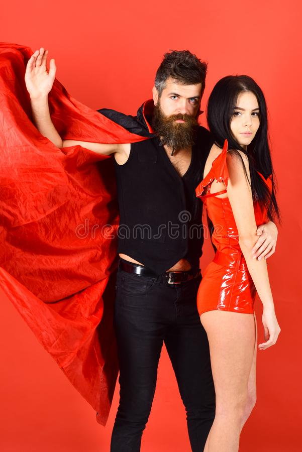 Attractive demon concept. Man and woman dressed like vampire, demon, red background. Couple on strict face play role royalty free stock image