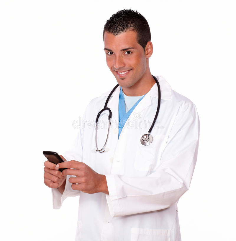 Attractive doctor guy texting a message. Portrait of attractive doctor guy sending a message with his cellphone while smiling at you and standing on isolated stock images