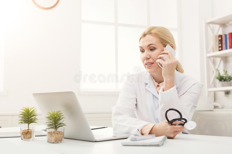 Attractive doctor talking on the phone with his patient stock photo