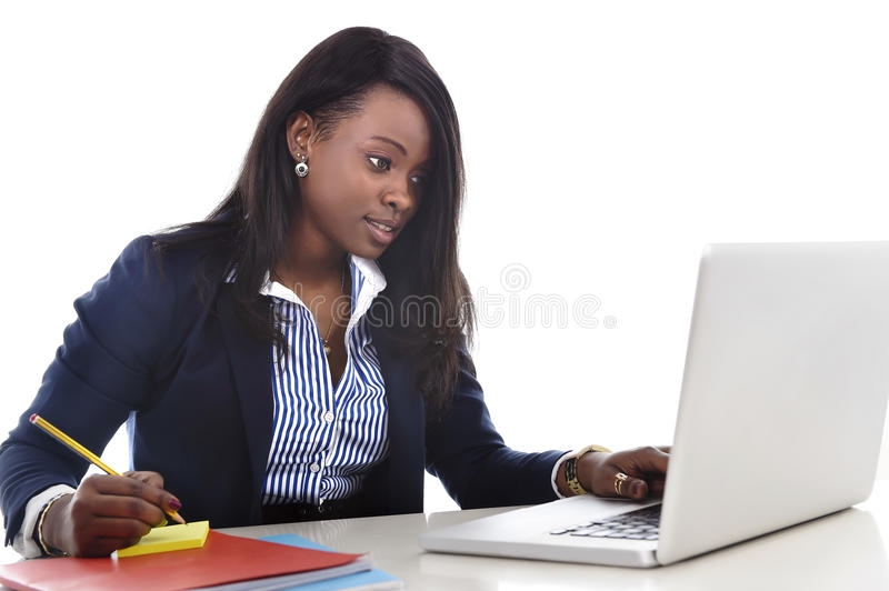Attractive and efficient black ethnicity woman sitting at office computer laptop desk typing stock photography