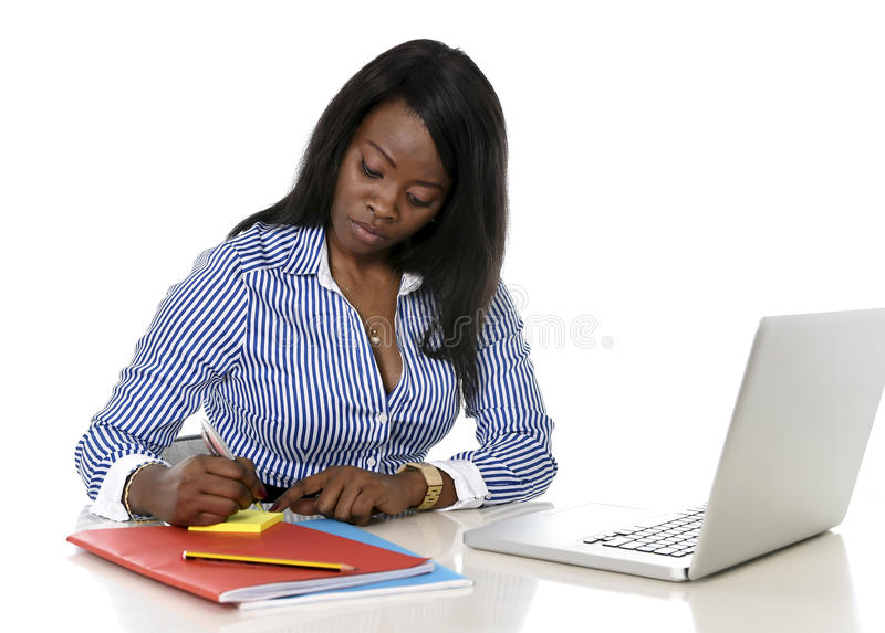 Attractive and efficient black ethnicity woman writing on notepad at office computer laptop desk stock photography