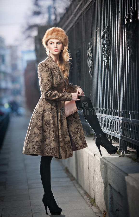Attractive elegant blonde young woman wearing an outfit with Russian influence in urban fashion shot. Beautiful fashionable girl stock photo