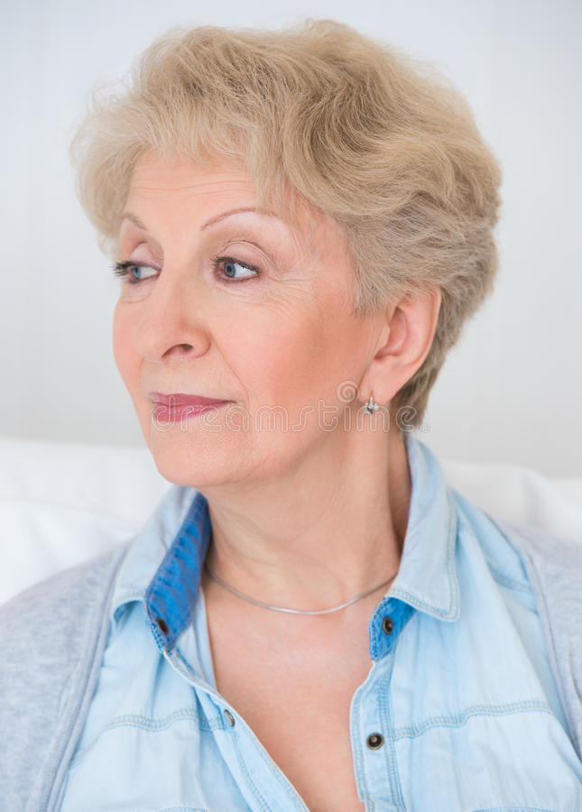 Attractive elegant senior woman daydreaming royalty free stock photography