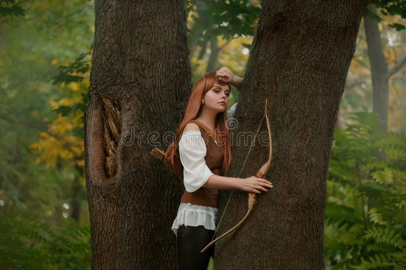 Attractive elven archer not ready to shoot a victim with a wooden bow arrow, a kind and sweet girl with long red hair in stock photography