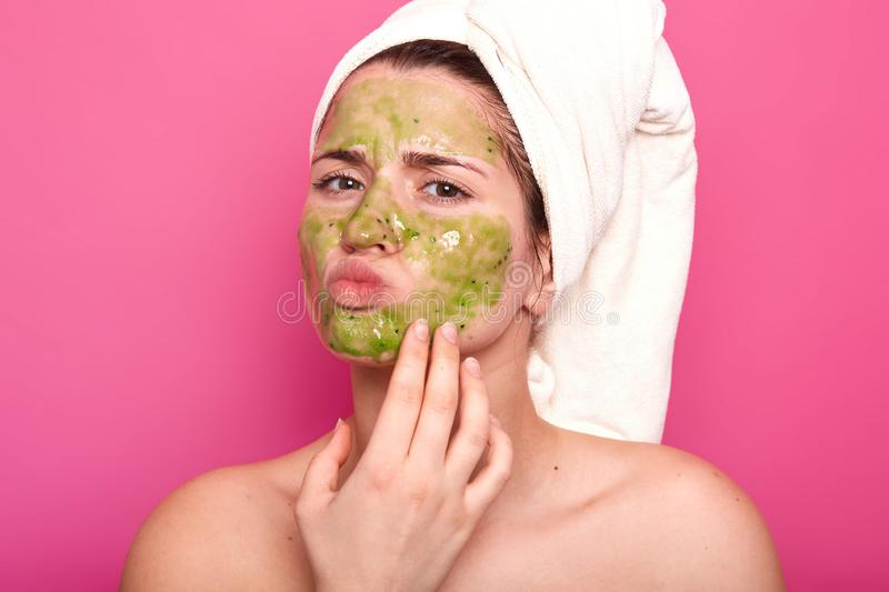 Attractive emotional young beauty has green mask on her face, day to have spa procedures, protrudes her lips, has unpleasant royalty free stock photos
