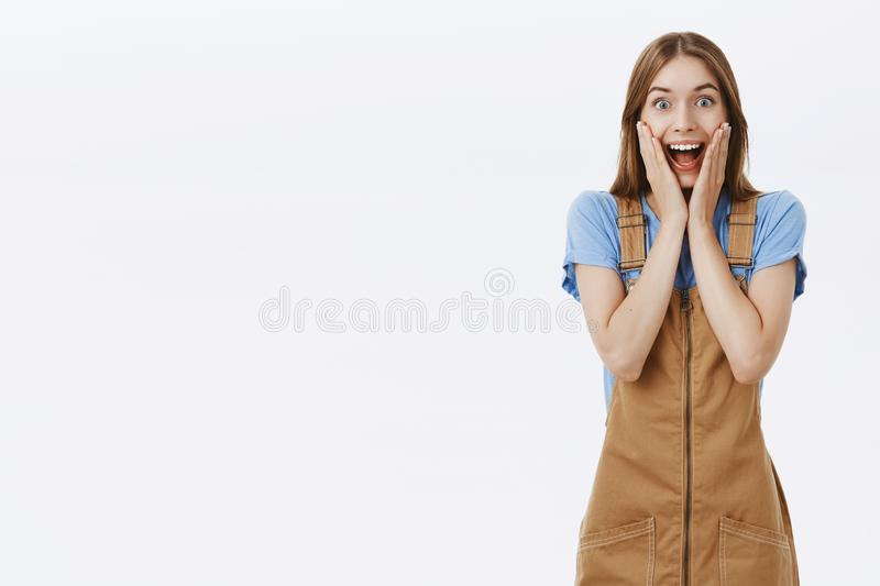 Attractive emotive girl reacting to awesome news. Portrait of impressed astonished happy girlfriend in brown trendy stock images