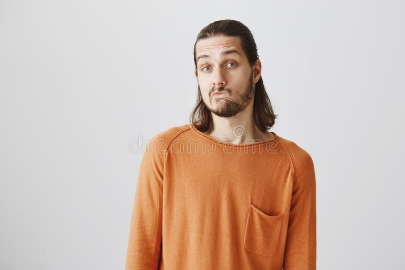 Attractive employer having doubts while thinking about his answer. Good-looking mature male with beard moving lips aside. Looking curious while hesitating stock image