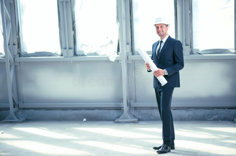Attractive engineer in helmet is building new stock photography