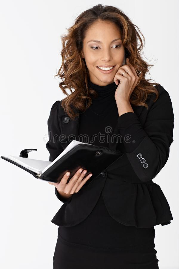 Attractive ethnic businesswoman on mobile smiling royalty free stock images
