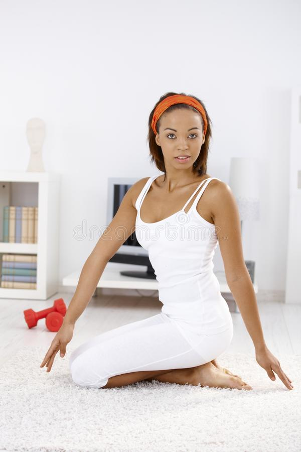 Attractive ethnic woman exercising at home. Attractive fit ethnic woman exercising at home on living room floor, looking at camera stock photos