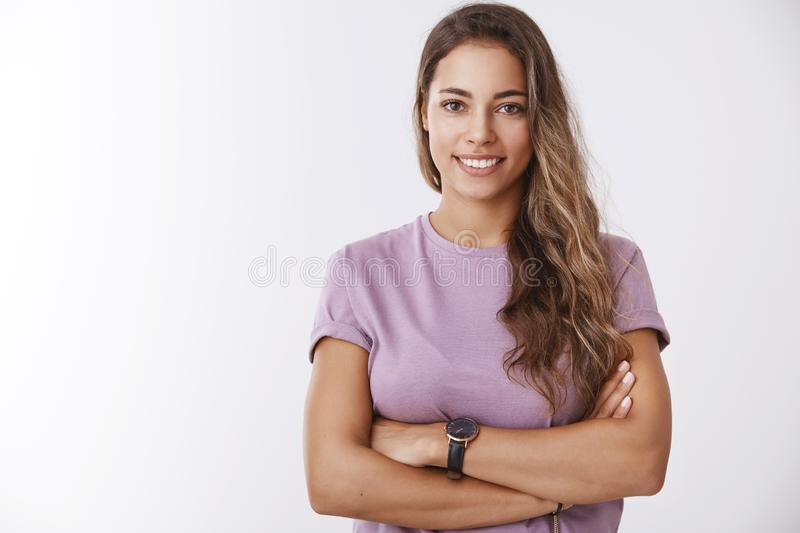 Attractive european curly-haired woman wearing purple t-shirt cross arms over chest confident smiling broadly, leading stock photo