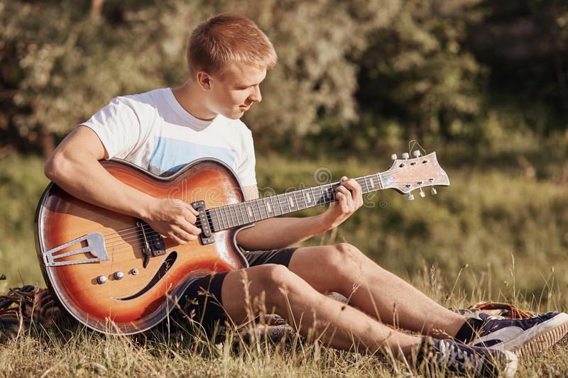 Attractive European male teenager sits on grass, plays acoustic guitar, recreats during summer day, practices new song, sings, enj stock photography