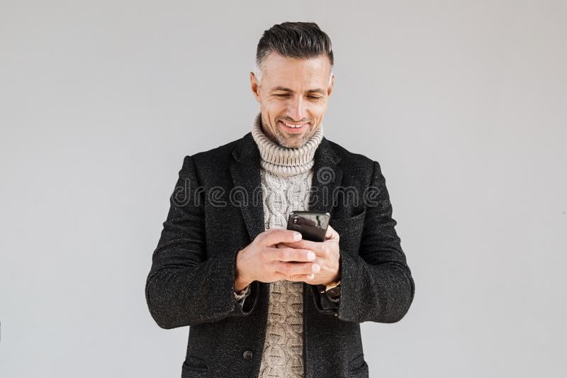 Attractive man wearing coat standing stock photo