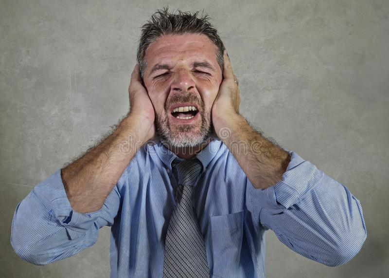 Attractive exhausted and stressed businessman in shirt and necktie suffering headache feeling overworked and overwhelmed screaming royalty free stock image