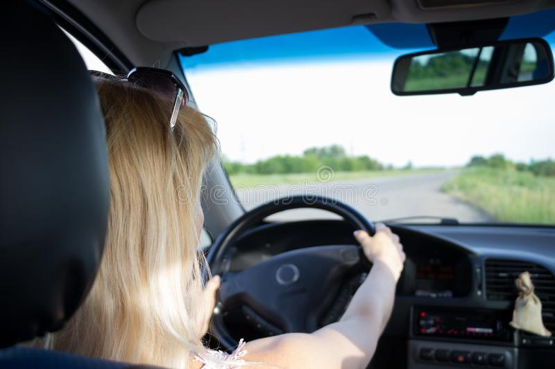 Attractive fair-haired girl keep both hands on steering wheel while driving an old car with black interior through the country royalty free stock images