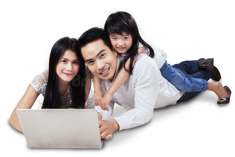 Attractive family with laptop in the studio. Happy family lying down on the floor while surfing on internet online with laptop, isolated over white stock photography