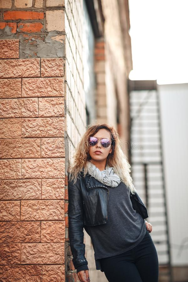 Attractive fashion model in mirrored sunglasses, a black leather jacket, black jeans near brick wall royalty free stock images