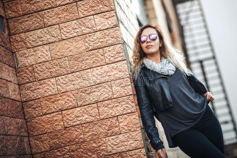 Attractive fashion model in mirrored sunglasses, a black leather jacket, black jeans near brick wall royalty free stock photos