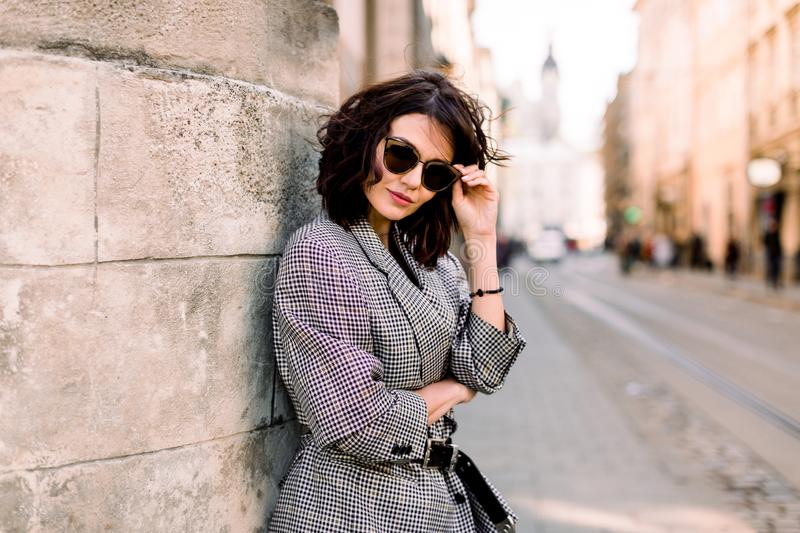 Attractive fashion modern woman in sunglasses standing on the city street. Summer portrait of happy girl on a walk stock photography