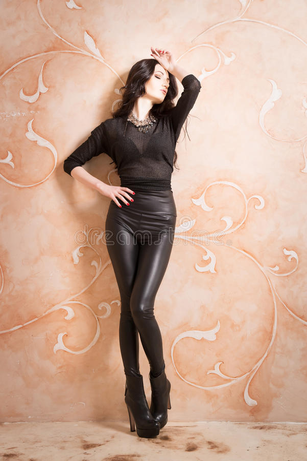 Attractive fashion woman in black leather pants royalty free stock image