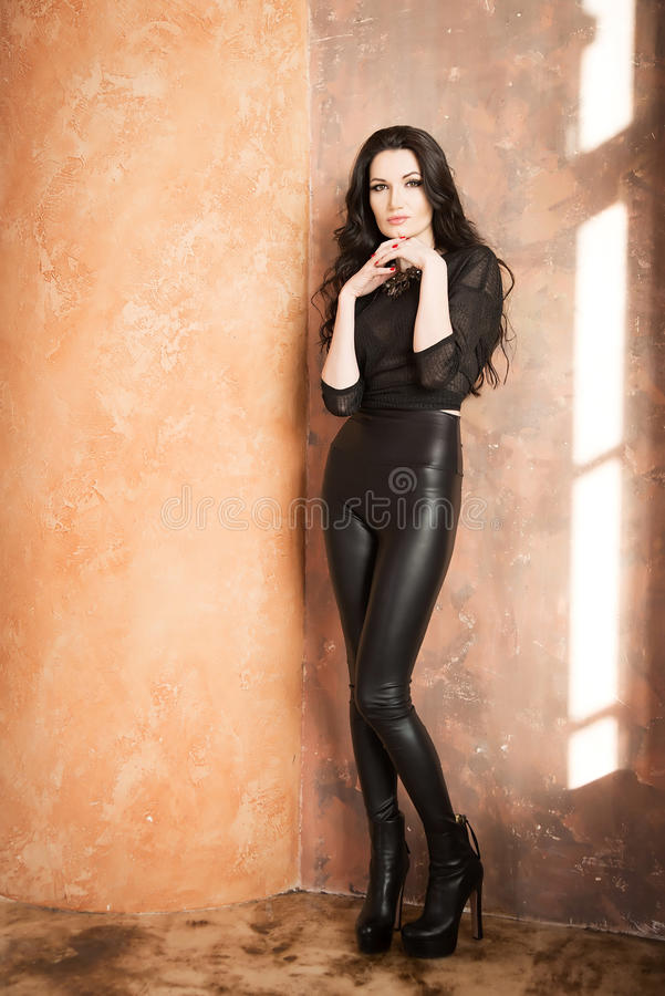 Attractive fashion woman in black leather pants. Indoor stock images