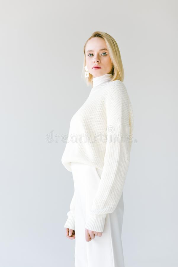 Attractive fashionable blonde woman in white clothes looking at camera. Isolated on white stock image