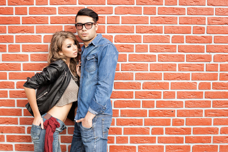 Attractive fashionable couple dressed casual. Attractive fashionable couple casually leaning against brick wall - landscape orientation stock image