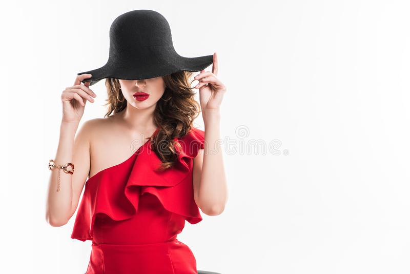 attractive fashionable girl hiding eyes under black hat royalty free stock photo