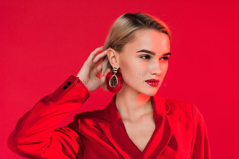 Attractive fashionable girl posing in red jacket and earrings,. Isolated on red royalty free stock images