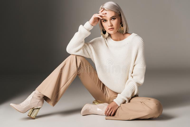 Attractive fashionable woman posing in white trendy sweater beige pants and autumn heels. On grey royalty free stock photography