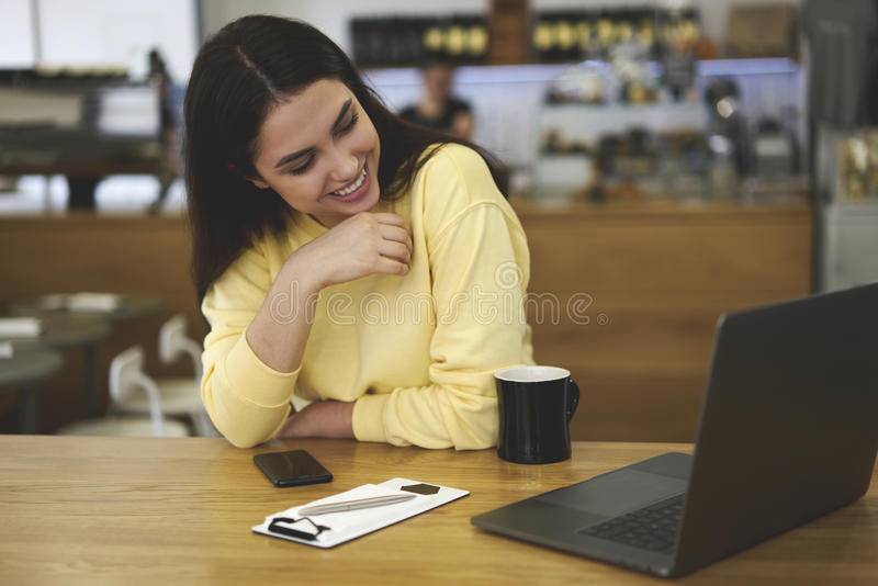 Attractive female administrative manager enjoying cup of aroma coffee royalty free stock photography