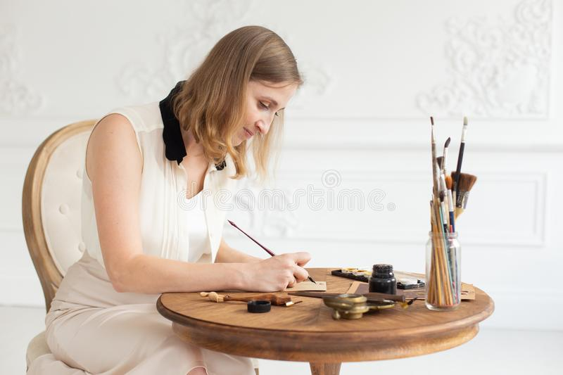 An attractive female artist sits at a table in an art workshop and draws a sketch of a drawing. royalty free stock photo