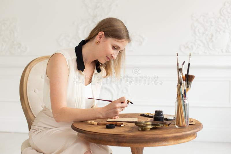 An attractive female artist sits at a table in an art workshop and draws a sketch of a drawing. stock photography