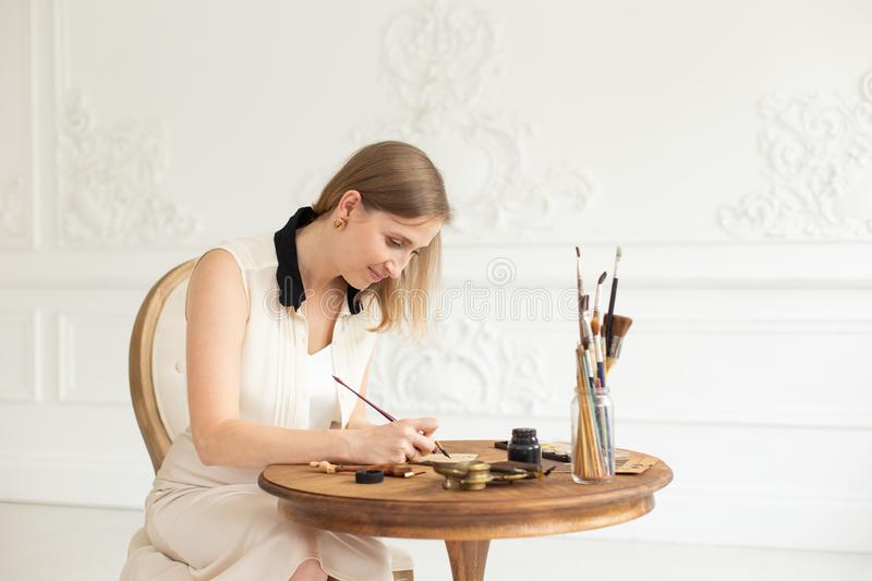 An attractive female artist sits at a table in an art workshop and draws a sketch of a drawing. royalty free stock image