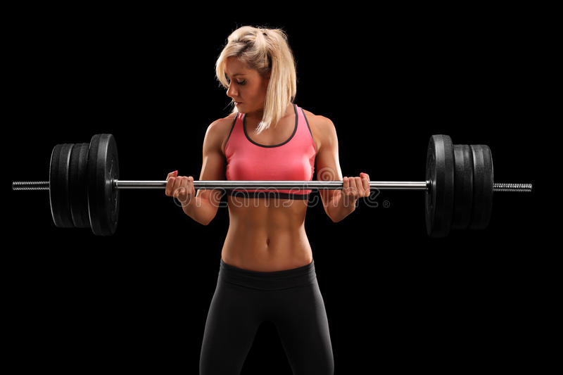 Attractive female athlete exercising with barbell. On black background stock photography