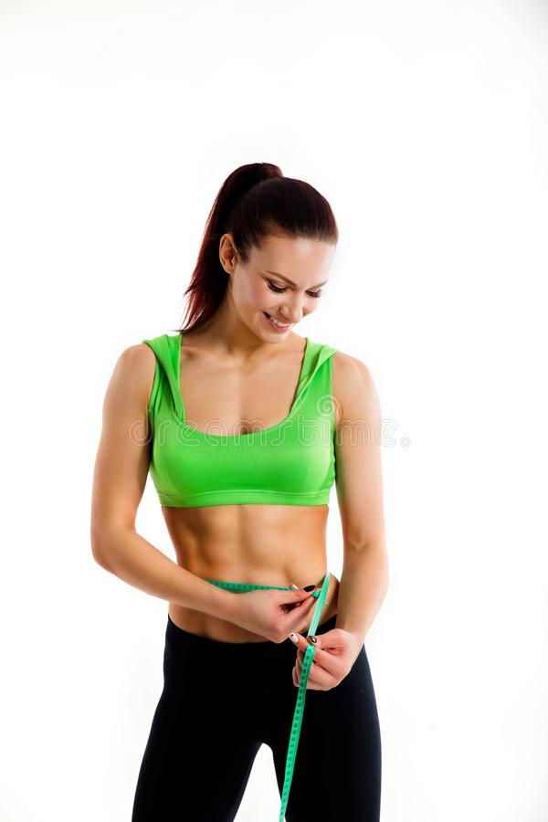 Attractive female bodybuilder measuring her waist with measurement tape. Photo of young woman in sportswear on white stock photography