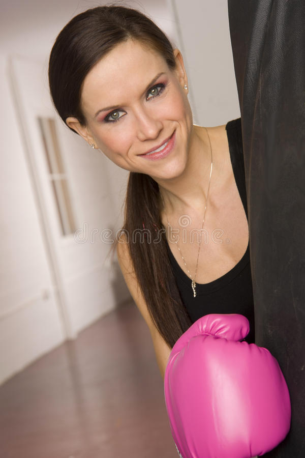 Attractive female boxer pink gloves heavy bag stock photos