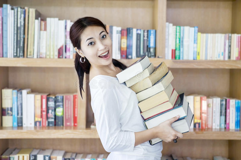 Attractive female bring stack of books in library royalty free stock image