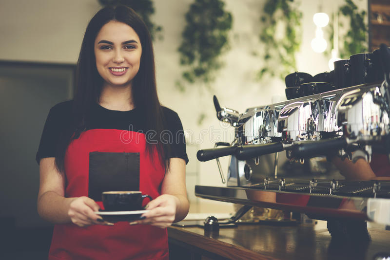 Attractive female businesswoman barista owner of bar caffe. Portrait of young attractive waitress holding americano for customer ordering dressed in brand royalty free stock photography