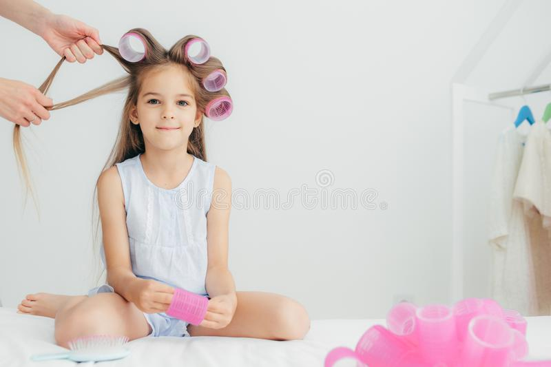 Attractive female child has curlers on head, going to have wonderful hairstyle, recieves beauty lessons from affectionate. Mother, isolated over white royalty free stock image