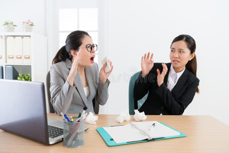 Attractive female company manager sneezing. And women co-worker looking at her feeling afraid when they having meeting in office stock photos