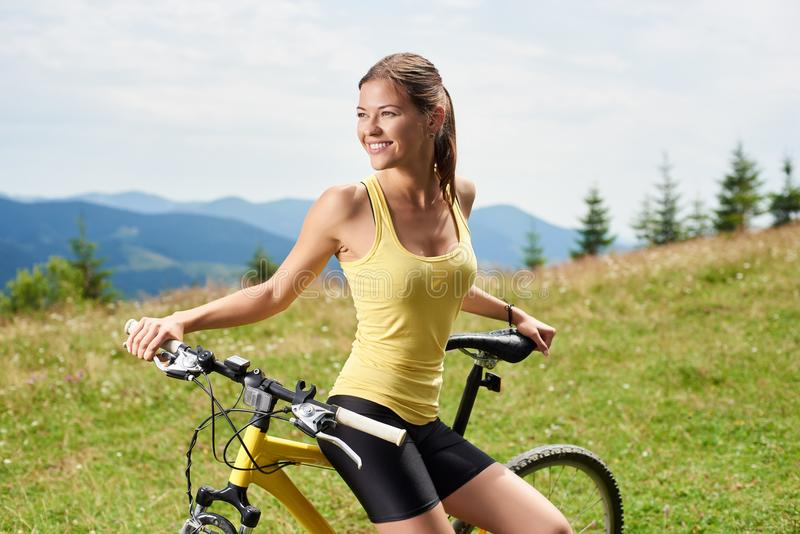 Attractive female cyclist with yellow mountain bicycle, enjoying sunny day in the mountains. Portrait of attractive happy woman cyclist resting on yellow royalty free stock photo